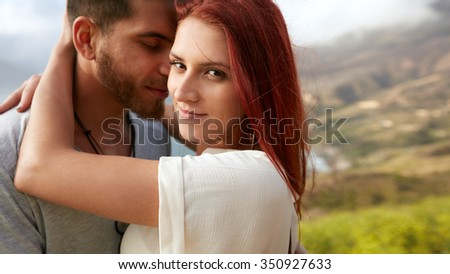 Closeup portrait of pretty young woman looking at camera while hugging her boyfriend outdoors. Romantic young couple together on vacation. - stock photo