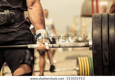 Closeup portrait of professional bodybuilder workout with barbell outdoors - stock photo