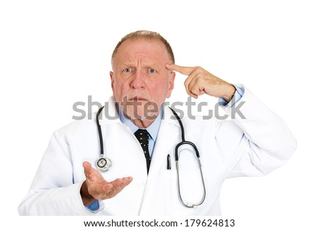 Closeup portrait of puzzled, confused senior doctor, old health care professional gesturing with finger against temple, asking question are you crazy? isolated on white background. Emotion, expression - stock photo