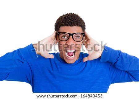 Closeup portrait of really stressed out young guy, handsome student wearing black glasses,closing ears because loud noise, isolated on white background. Negative human emotions, facial expressions - stock photo