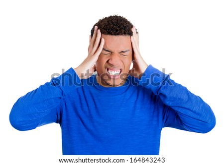 Closeup portrait of really stressed out young guy, handsome student with headache, wearing blue sweater, having a bad day, isolated on white background. Negative human emotions and facial expressions - stock photo