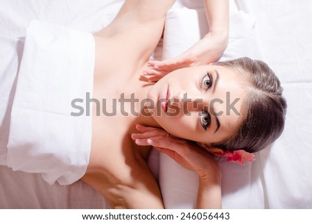 closeup portrait of relaxed beautiful lady lying on her back and looking at camera during massage treatment  - stock photo