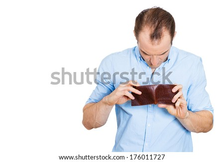 Closeup portrait of sad, upset, unemployed broke guy, fired employee, jobless business man, holding looking into his empty wallet, isolated on white background. Bankruptcy, financial problems mistakes - stock photo