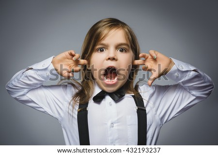 Closeup portrait of screaming girl covering her ears, observing. Hear nothing. Human emotions, facial expressions - stock photo