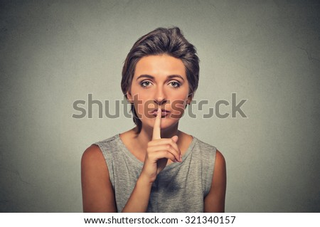 Closeup portrait of secret woman. Young female showing hand silence sign, asking someone to keep it quiet, isolated on gray background. Human communication, facial expressions signs - stock photo