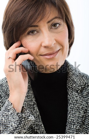 Closeup portrait of senior businesswoman talking on mobile phone. Isolated on white background. - stock photo