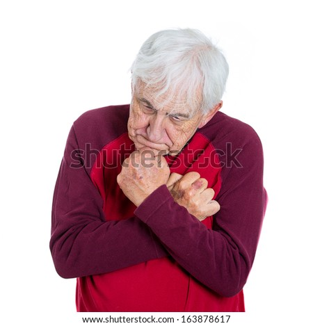 Closeup portrait of senior citizen elderly mature retired grandfather grandpa man in red shirt holding his arms fists tightly close to chest shaking unable to straighten, isolated on white background - stock photo