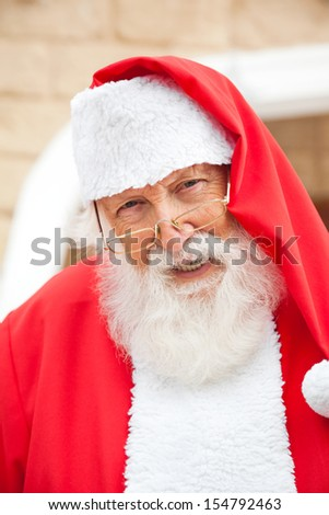 Closeup portrait of senior man dressed as Santa Claus smiling outdoors - stock photo