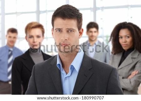 Closeup portrait of serious young businessman and team at office. - stock photo
