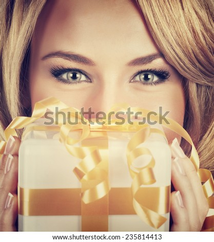 Closeup portrait of sexy woman with beautiful eyes holding in hands Christmas gift, receive romantic present, perfect festive makeup, luxury New Year celebration - stock photo
