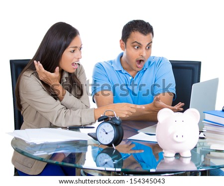 Closeup portrait of shocked attractive man and woman looking at bill on laptop, isolated on white background - stock photo