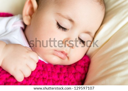 Closeup portrait of sleeping baby in pink knitted  blanket - stock photo