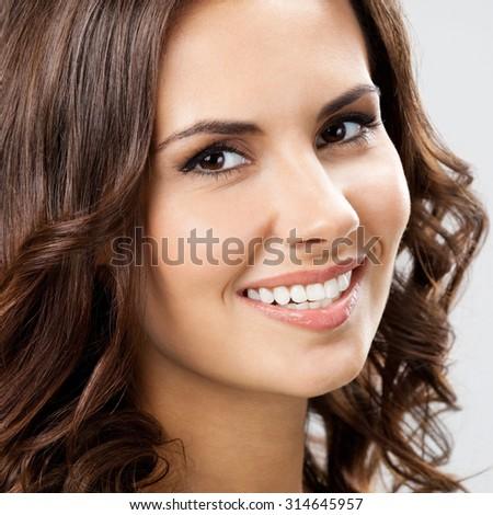 closeup portrait of smiling beautiful young woman - stock photo