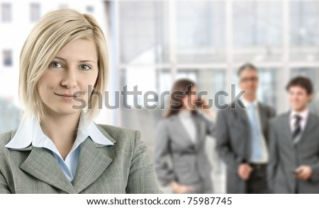 Closeup portrait of smiling businesswoman with coworkers in background.? - stock photo