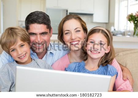 Closeup portrait of smiling family with laptop in house - stock photo
