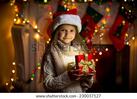 Closeup portrait of smiling girl opening sparkling gift box at Christmas - stock photo