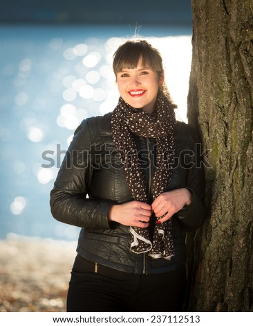 Closeup portrait of smiling woman in jacket posing on riverbank at autumn sunny day - stock photo