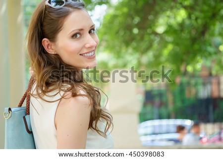 Closeup portrait of smiling youn brunette woman looks back - stock photo