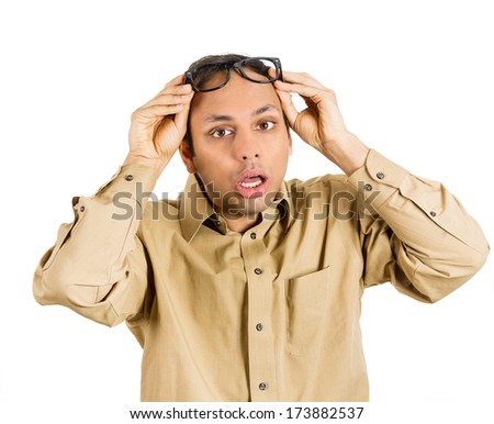 Closeup portrait of stressed, anxious, overwhelmed young guy, student, teacher, worker, employee, looking completely lost, holding his glasses, can't believe  bad news he just received. Human emotions - stock photo