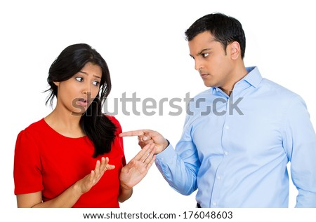 Closeup portrait of stressed, arguing young couple having serious problems fighting, isolated white background .Woman victim of domestic violence and abuse. Husband placing blame and pointing fingers - stock photo