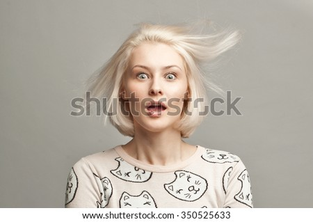 closeup portrait of surprised young blonde woman on gray background - stock photo
