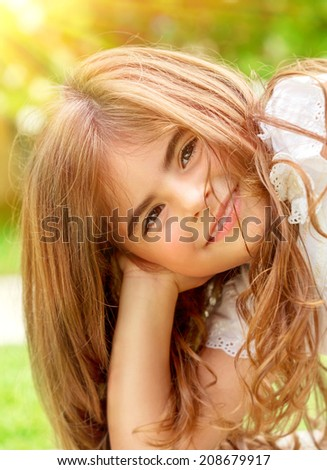 Closeup portrait of sweet little child outdoors, cute Arabic girl enjoying warm sunny summer day, happy and carefree childhood concept - stock photo