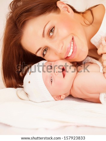 Closeup portrait of sweet newborn baby with pretty mom, healthy childhood, young family, happy motherhood, tenderness and love concept - stock photo