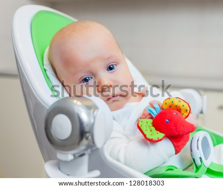 Closeup portrait of sweetest baby playing with a colorful mobile toy - stock photo