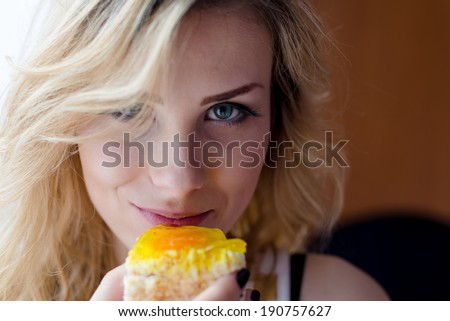 closeup portrait of tasting delicious cake beautiful young woman sexy blond girl happy smiling and looking at camera picture - stock photo