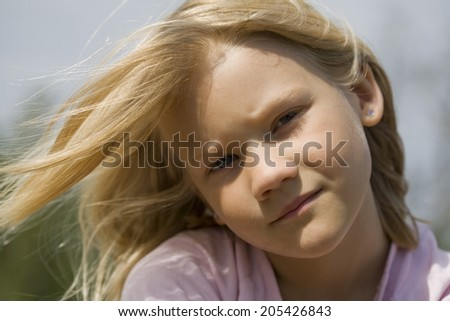 Closeup portrait of thoughtful looking young scandinavian girl outdoors on sunny summer day with wind blowing hair - stock photo