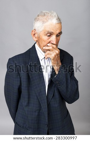 Closeup portrait of thoughtful old man  over gray background - stock photo