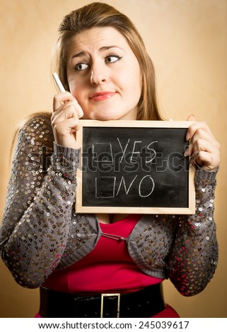 Closeup portrait of thoughtful woman holding blackboard with yes and no options - stock photo