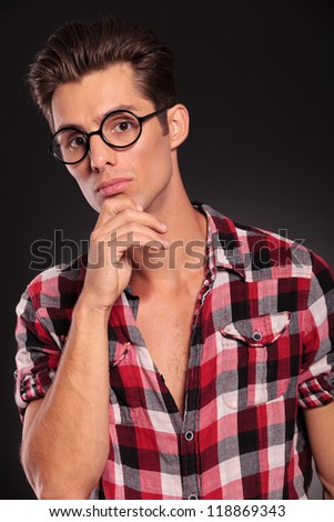 Closeup portrait of thoughtful young man in glasses against white background - stock photo