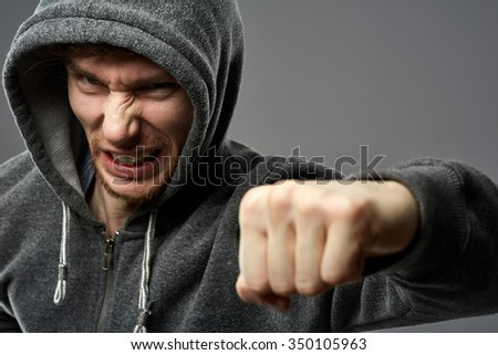 Closeup portrait of threatening gangster wearing a hood, representing the concept of danger - stock photo