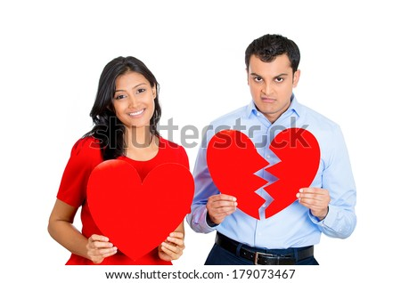 Closeup portrait of two people, depressed man, happy pretty excited woman holding big red heart, other showing broken ripped one. Relationship contrast. Negative emotions, facial expressions, feeling. - stock photo