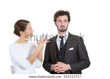 Closeup portrait of two people, man and woman, wife accusing husband in wrong doing, pointing finger at him, he is in denial, but looking embarrassed and ashamed, isolated on white background. Concept - stock photo