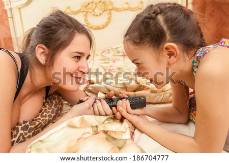 Closeup portrait of two sisters looking at each other and pulling TV remote - stock photo