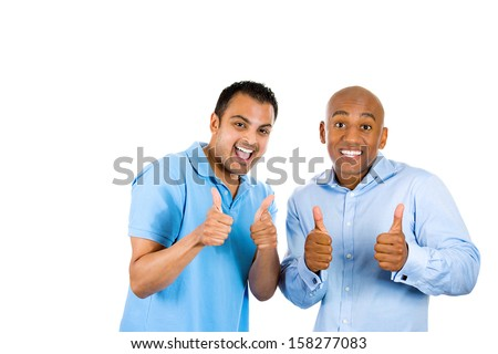 Closeup portrait of two young friendly men, happy coworkers; smiling young business partners, students giving thumbs up sign, isolated on white background with copy space. Corporate life, deal making - stock photo