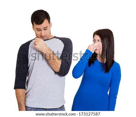 Closeup portrait of woman closing her nose, something stinks, very bad smell, odor. Guy sniffs himself. Isolated on white background. Negative emotion facial expression feeling. Unpleasant situation - stock photo