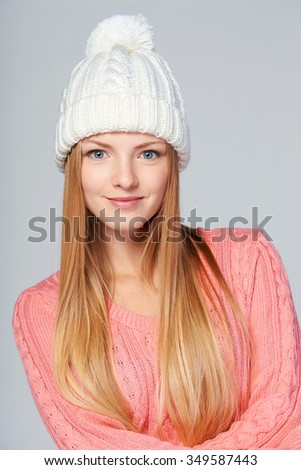 Closeup portrait of woman wearing woolen hat and sweater with amazement on her face - stock photo