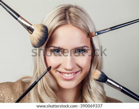 Closeup portrait of woman with makeup brushes near face - stock photo