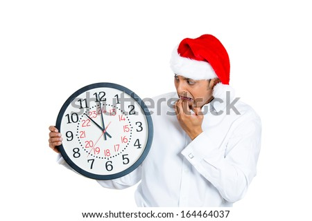 Closeup portrait of worried young man wearing red santa claus hat, hands in mouth holding clock, isolated on white background. Negative emotion facial expression. Last minute christmas shopping - stock photo