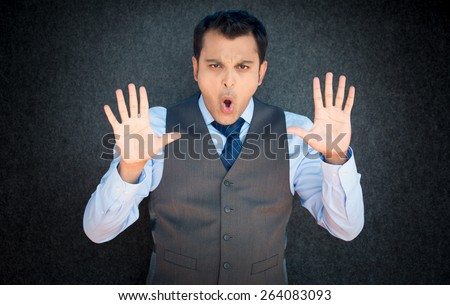 Closeup portrait of young, angry man in vest and blue tie, gesturing no with hands and saying stop with his mouth, isolated on gray black background - stock photo