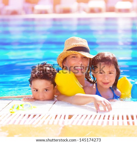 Closeup portrait of young Arabic mother with two adorable children swimming in the pool, happy family on beach resort, happy summer holidays - stock photo