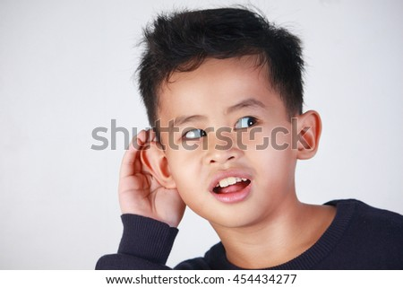closeup portrait of young Asian boy listening carefully with his hand to ear gesture trying to hear secretly interesting information conversation news - stock photo