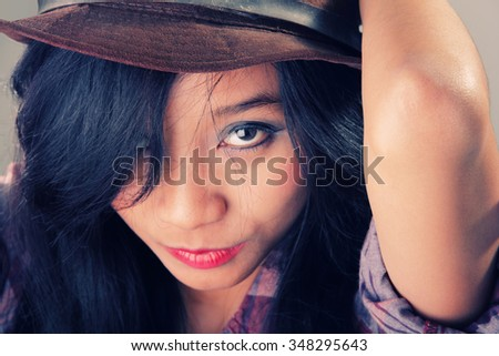 Closeup portrait of young Asian female model in mysteriously seductive pose - stock photo