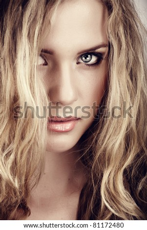 closeup portrait of young beautiful blonde woman with long curly hair and natural fresh make-up and summer tan - stock photo