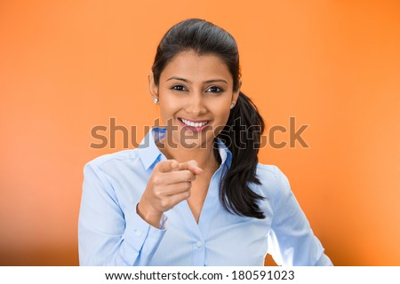 Closeup portrait of young, beautiful, excited, happy woman smiling, laughing, pointing finger towards you, camera gesture, isolated on orange red background. Positive human emotion, attitude, reaction - stock photo