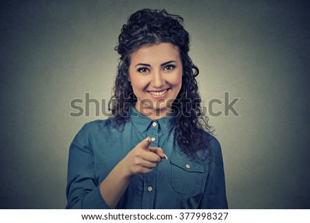 Closeup portrait of young, beautiful, excited, happy woman smiling, laughing, pointing finger towards you, camera gesture, isolated on gray wall background. Positive human emotion, attitude, reaction - stock photo