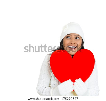 Closeup portrait of young beautiful pretty woman wearing winter gear attire sweater holding red valentine heart looking up, isolated on white background. Positive emotion facial expression feelings. - stock photo